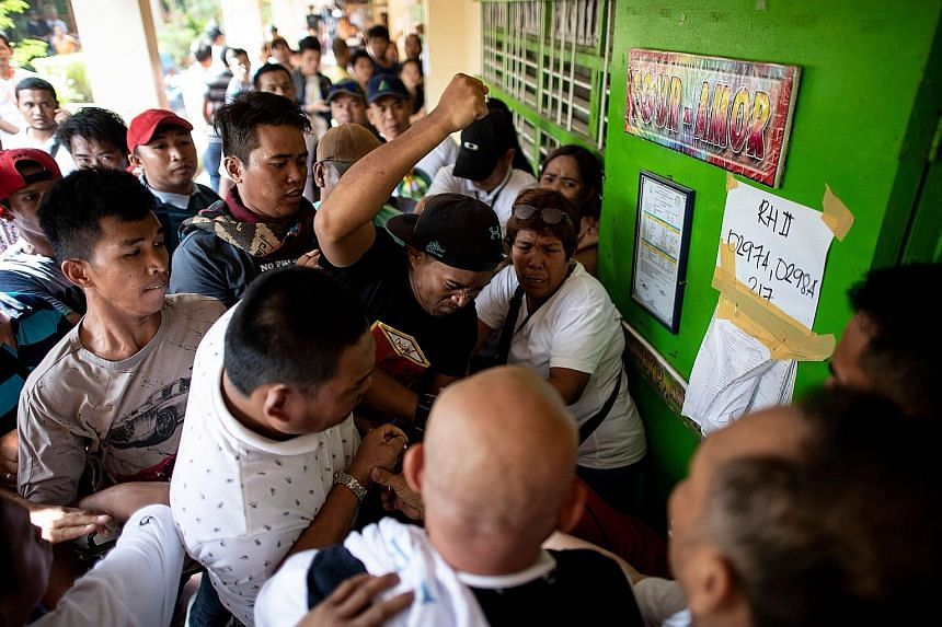 "A crowd of voters attacking a person (hidden) accused of casting multiple votes yesterday in Cotabato, Mindanao. Officials said the referendum was uneventful overall despite reports of ""flying voters"" and harassment of poll officials."