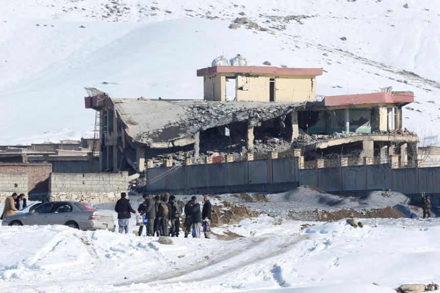 Afghan men stand in front of a collapsed spy agency base after a car bomb attack in Wardak, Afghanistan, on Jan 21, 2019.