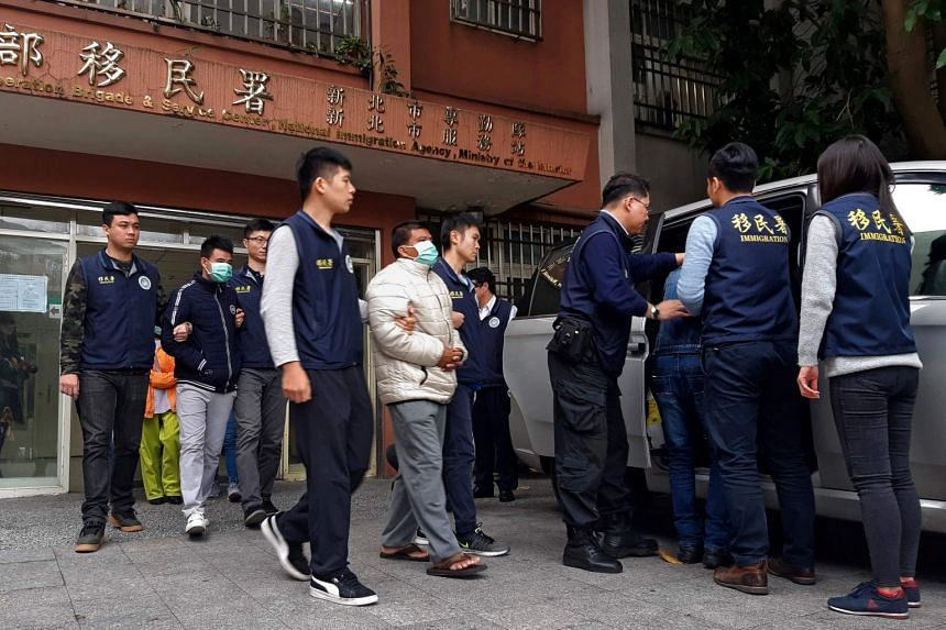 Taiwanese immigration officers escort three detained men (with masks), believed to be some of the 152 Vietnamese who went missing after arriving on the island, into a vehicle outside the immigration offices on Dec 28, 2018.