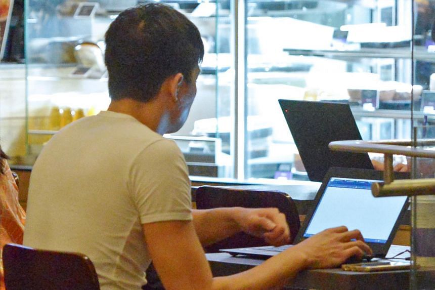 File photo showing a man using a laptop at a cafe. At least four reports of such tech support scams have been made in January.