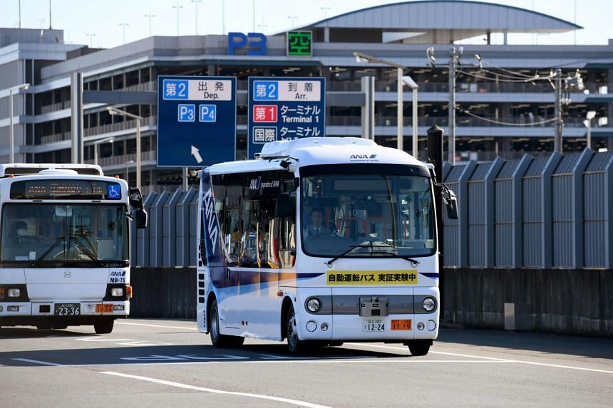 """A driverless bus moves during an open test drive at Tokyo's Haneda International airport on Jan 22, 2019. The """"driver"""" is seated with his hands above the wheel, allowing the bus to wend the route on its own."""