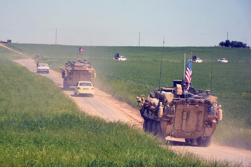 File photo of a convoy of US army troops and the People's Protection Units Kurdish militia patrol near al-Ghanamya village, near the Syrian-Turkish border, in Syria.