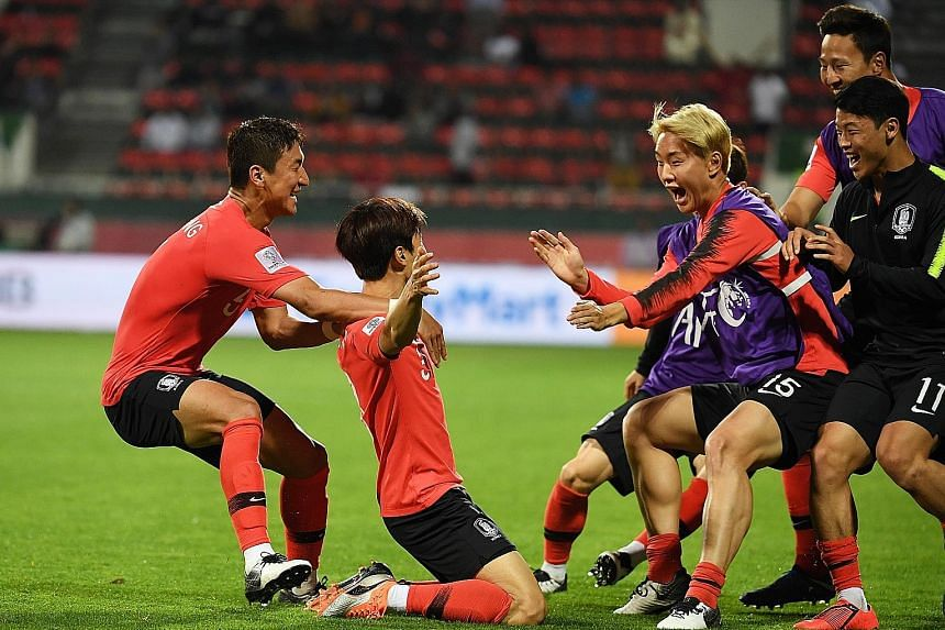 South Korean players celebrate substitute Kim Jin-su's (kneeling) extra-time goal against Bahrain. The left-back's header sent the Koreans through to the quarter-finals with a 2-1 win.