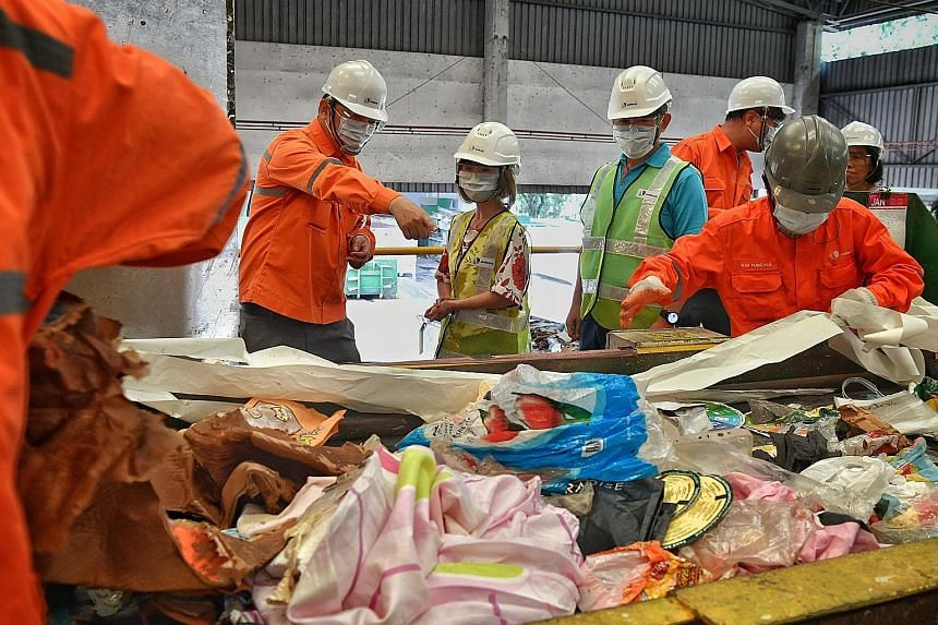 Above: Dr Amy Khor, Senior Minister of State for the Environment and Water Resources, flanked by Mr Tan Chee Boon (in orange), manager (Recovery) of Sembcorp Environment, and Mr Neo Hong Keat, senior vice-president of SembWaste, watching workers sort