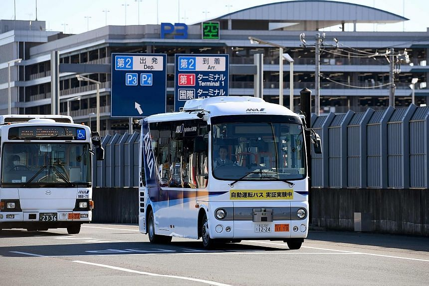 An operator monitors the minibuses (right) as they cruise along a route at a speed of up to 30kmh using GPS and magnetic road markers.