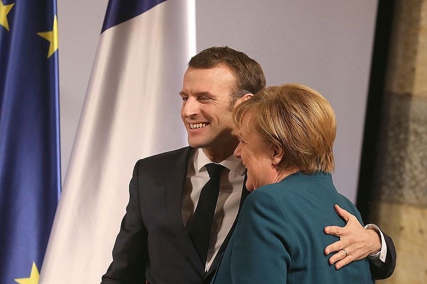 French President Emmanuel Macron and German Chancellor Angela Merkel sharing a hug yesterday at the town hall of Aachen, where they signed the Treaty of Aachen. The agreement signals that Berlin and Paris will combat efforts by some nationalist polit