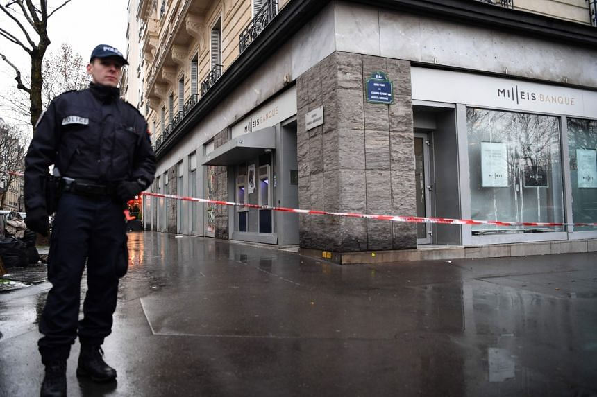 French police cordon off the area around the Milleis Banque close to the Champs-Elysees Avenue in central Paris.