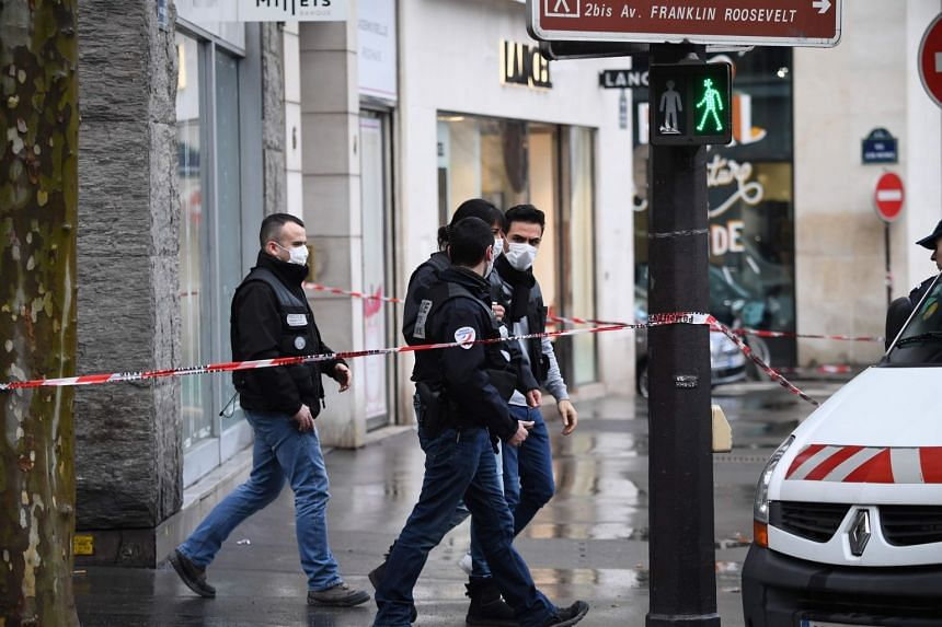 French police walk behind a cordoned off area, past the entrance to the Milleis Banque,