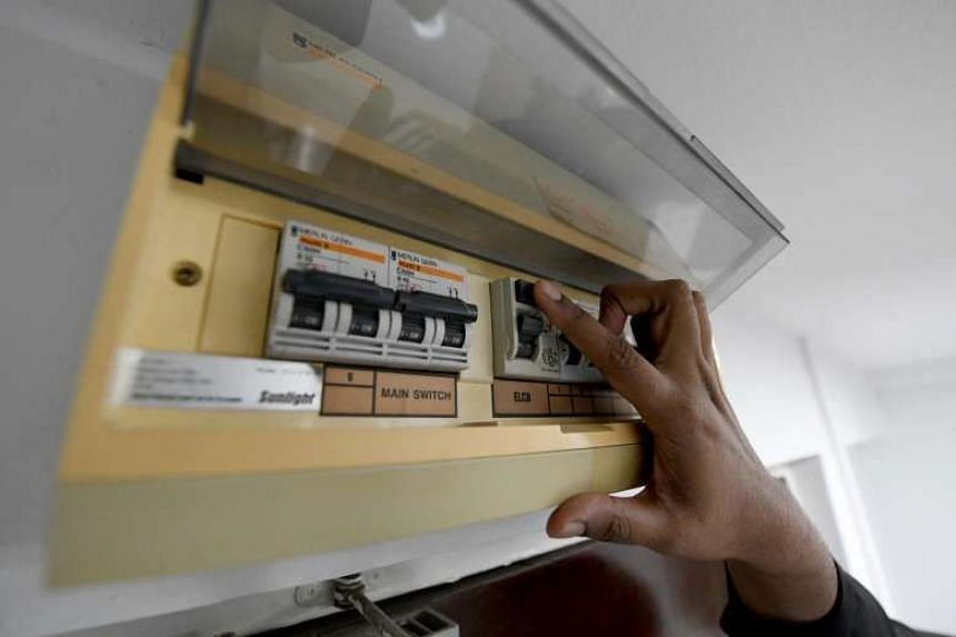 File photo showing a man flipping a switch on an electrical board.