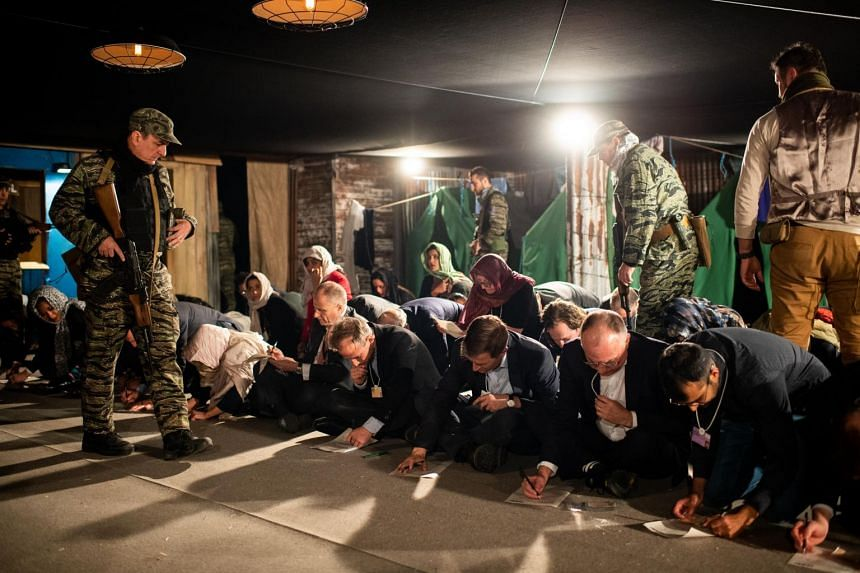 Actors playing soldiers and participants playing refugees attend the A Day in the Life of a Refugee session as part of the Annual Meeting 2019 of the World Economic Forum.