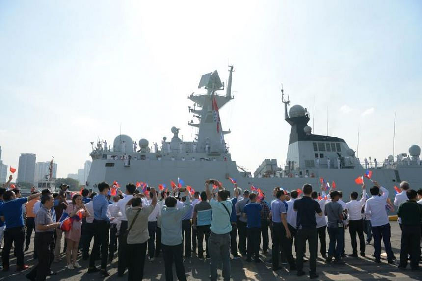 People waving flags of the Philippines and China as the Chinese guided-missile frigate Wuhu prepares to dock in Manila on Jan 17, 2019.