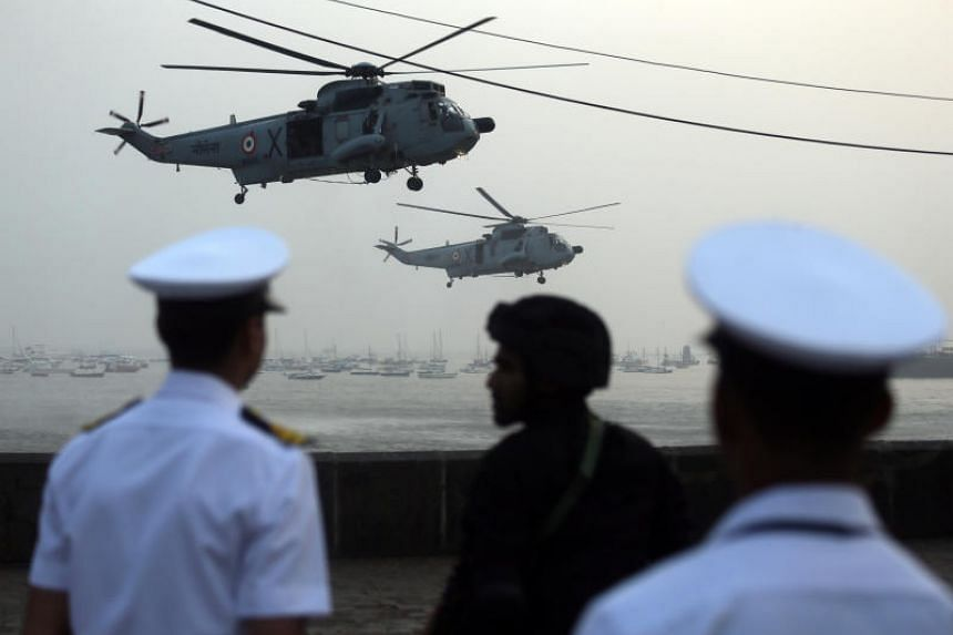 Indian Navy soldiers watch as helicopter pilots perform manoeuvres ahead of Navy Day celebrations in Mumbai, India, on Dec 3, 2018.