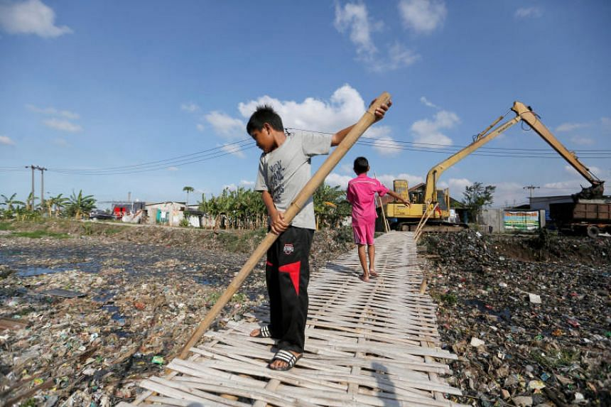 A boy uses a bamboo stick to clean a river covered in rubbish in Bekasi, West Java province, Indonesia, on Jan 7, 2019.