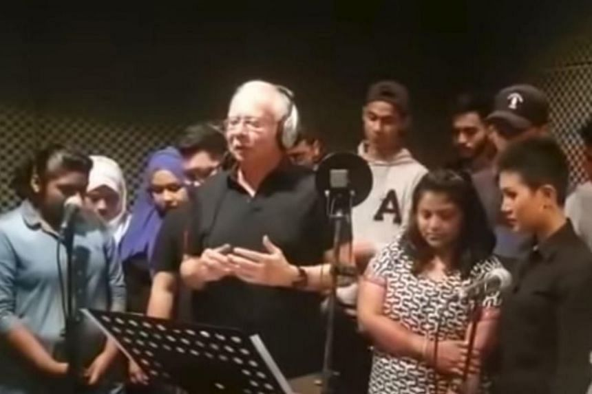 Video screengrab showing former Malaysian prime minister Najib Razak singing and swaying in the company of 15 other people.