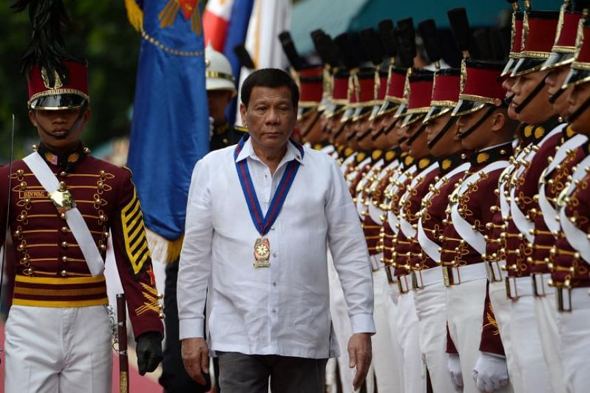 Philippine President Rodrigo Duterte reviews an honour guard at the national police headquarters in Manila, on Aug 8, 2018.