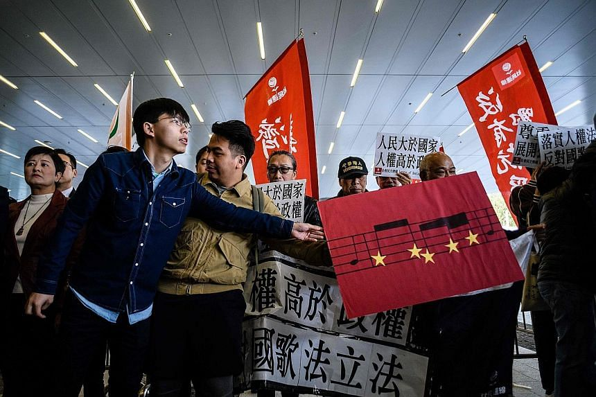 A pro-democracy activist passing a placard depicting part of the musical score of the Chinese national anthem, during a protest outside the Legislative Council in Hong Kong yesterday. The protest was against a proposed law that prescribes jail terms