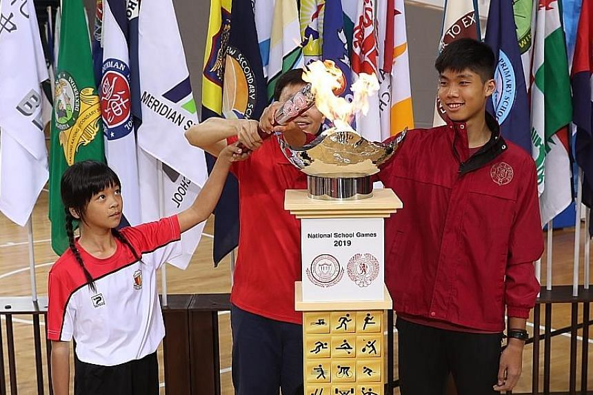 Tia Foong Po Shiun (left) from Haig Girls' School's football team and Victoria Junior College's high jumper Kampton Kam jointly lighting the torch with Senior Minister of State for Education Chee Hong Tat at yesterday's opening of the National School