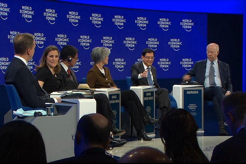 Finance Minister Heng Swee Keat speaking at the panel discussion at the World Economic Forum in Davos yesterday. With him were (from left) panel moderator and WEF president Borge Brende, Canada's Foreign Minister Chrystia Freeland, Japan's Foreign Mi