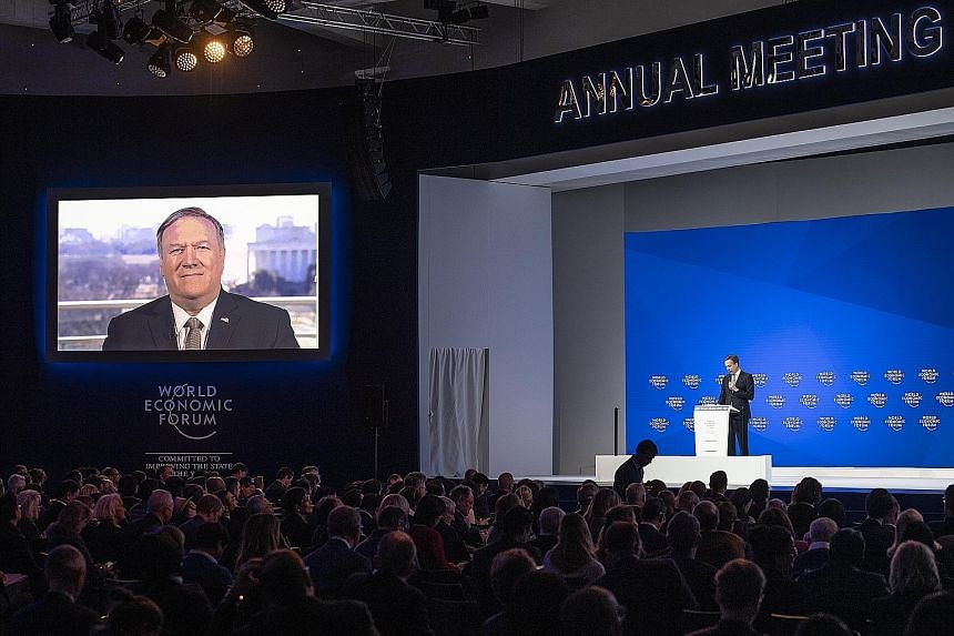 Mr Mike Pompeo (on screen), addressing the World Economic Forum via video, and WEF president Borge Brende (on stage) at the annual Davos summit of big business on Tuesday.