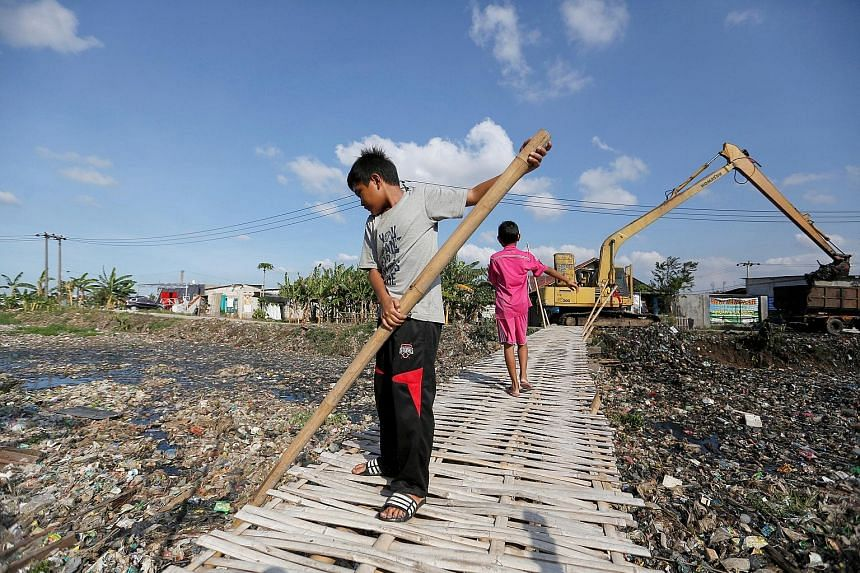 A boy using a bamboo stick to clean a river covered by rubbish in Bekasi, West Java, earlier this month. The river is among several in Indonesia thickly carpeted with trash formed mostly of plastic waste. The country is battling a lack of environment