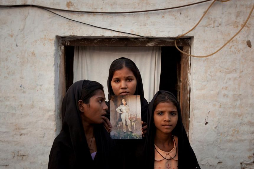 The daughters of Pakistani Christian woman Asia Bibi pose with an image of their mother while standing outside their residence in Sheikhupura, in Punjab, Pakistan, on Nov 13, 2010.