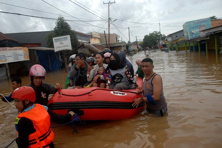 Rescue workers evacuate residents following floods in Makassar, South Sulawesi, Indonesia, on Jan 23, 2019.