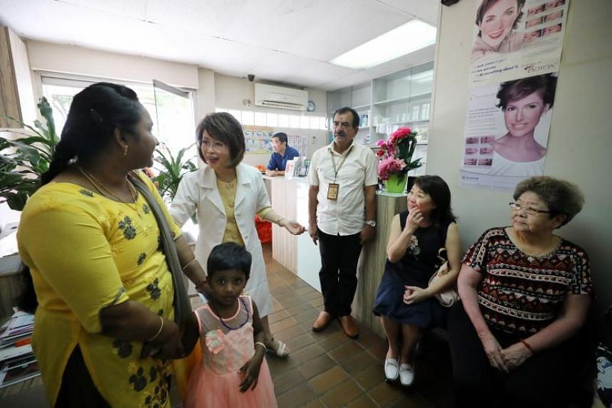 Dr Lily Neo speaking to software engineer Manju Somanathan (left, in yellow), 34, and her daughter Keerti, 3, and other patients in her clinic.