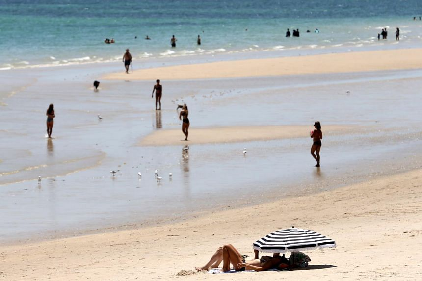Beachgoers cool off at Brighton beach during a hot day in Adelaide, South Australia, Australia, on Jan 22, 2019.