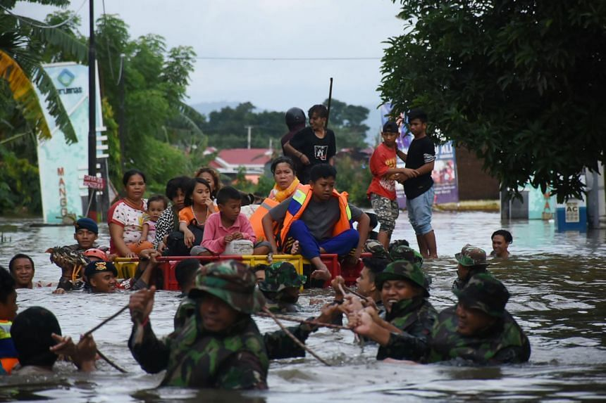 Indonesian soldiers evacuate flood-affected residents in Makassar, on Jan 23, 2019.