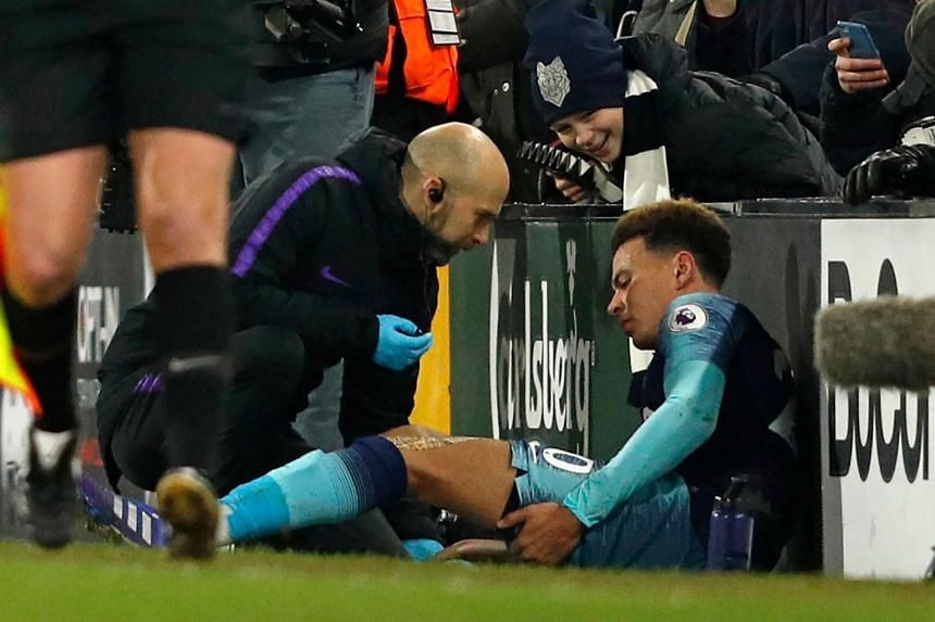Tottenham Hotspur's English midfielder Dele Alli (right) receives medical attention as he holds his leg after appearing to pick up an injury during the English Premier League football match between Fulham and Tottenham Hotspur, on Jan 20, 2019.