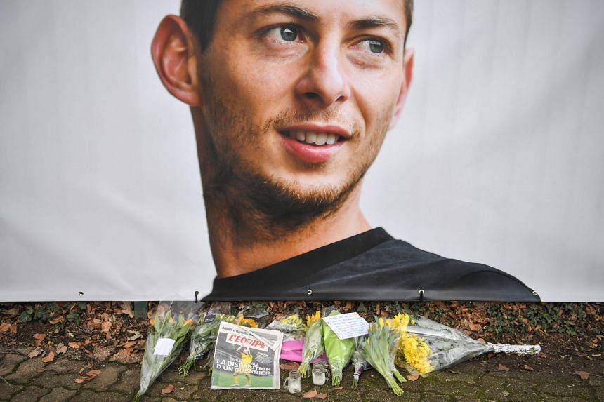 "Flowers and candles are left with the front page of French sports daily newspaper L'Equipe reading ""The disappearance of a warrior"" next to a portrait of Emiliano Sala in front of the entrance of the FC Nantes football club training centre."