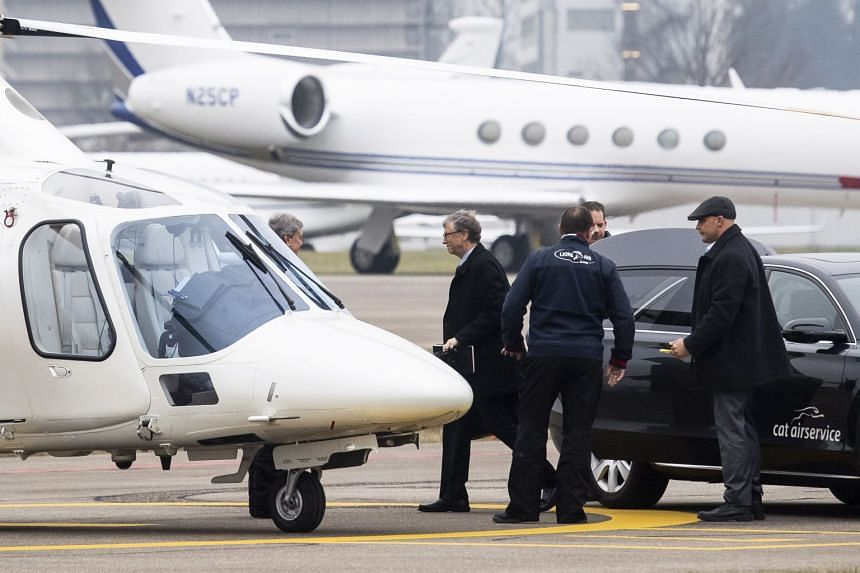 Bill Gates (centre) boards a helicopter to the World Economic Forum on the tarmac of Zurich Airport, in Ruemlang, Switzerland.