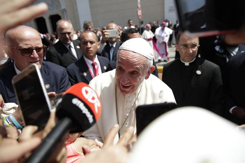 Pope Francis (centre) greets people as he leaves a meeting with Central American bishops in Panama City.