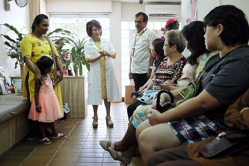Dr Lily Neo speaking to software engineer Manju Somanathan (far left) and her daughter Keerti Arivazhagan, and other patients in her clinic.