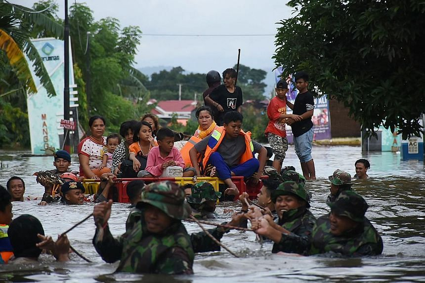 Indonesian soldiers evacuating residents in Makassar on Wednesday. More than 3,000 people have been evacuated and at least 46 are being treated at local hospitals and health clinics, as heavy rain and strong winds pounded the southern part of Sulawes
