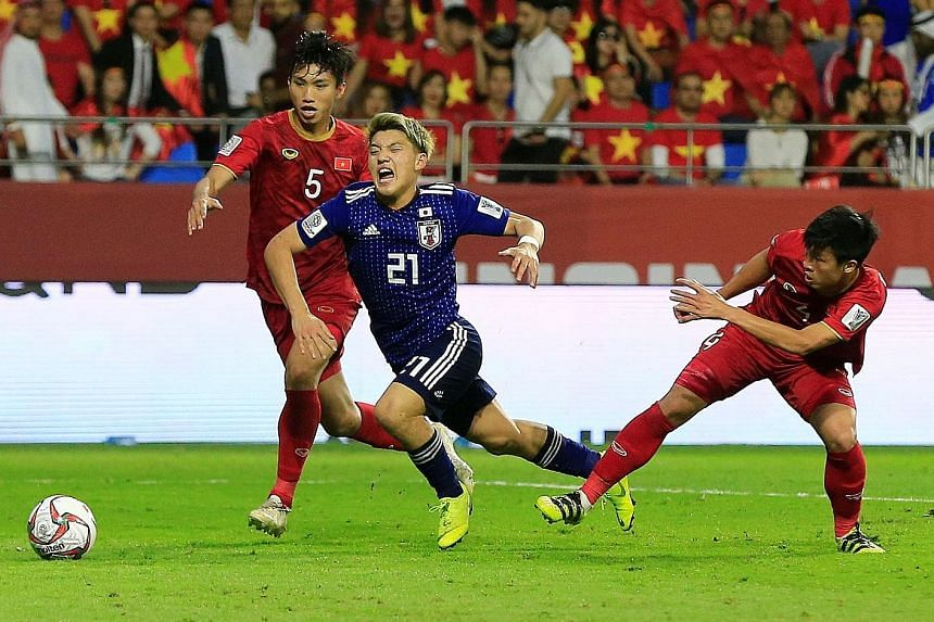 Japan's Ritsu Doan is fouled by Vietnam's Bui Tien Dung, resulting in a penalty being awarded after a VAR review. Doan converted the spot kick to send his team into the semi-finals.