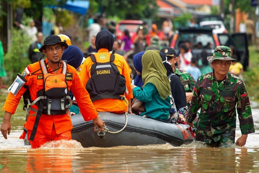 Indonesian rescuers evacuate residents from their homes in Makassar on Jan 24, 2019, as heavy rain and strong winds pounded the southern part of Sulawesi island.
