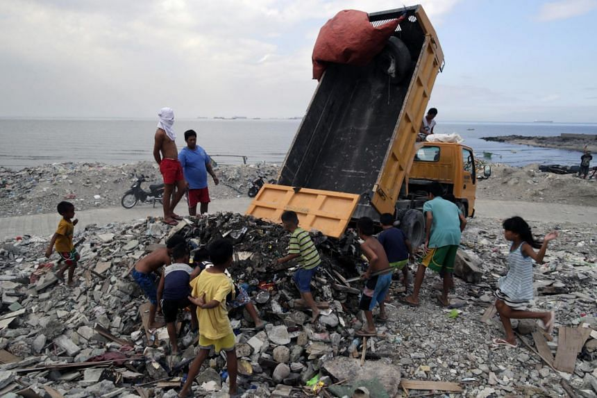 Filipino informal settler children collect recyclable materials among trash at a dumping area along the Manila Bay, on Jan 24, 2019.