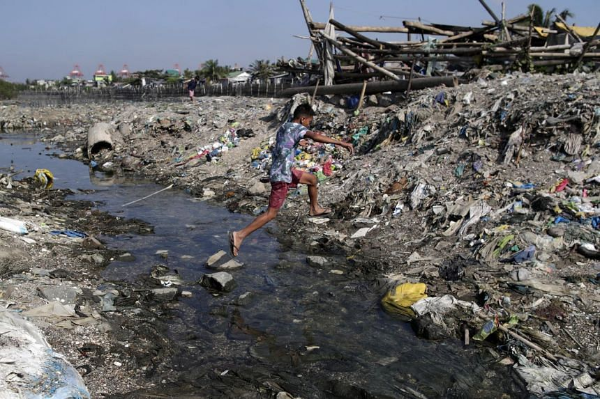 A boy crosses a waterway full of trash along Manila Bay, the Philippines, on Jan 17, 2019.