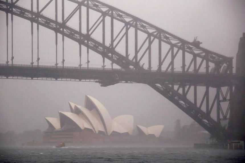A boat passes under the Sydney Harbour Bridge and in front of the Sydney Opera House, on Nov 28, 2018.