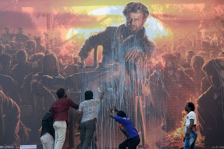 Indian fans spray milk on a billboard displaying the picture of Bollywood star Rajinikanth, on Jan 10, 2019.