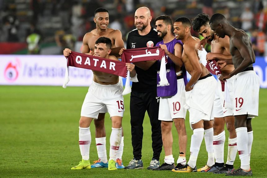Qatar's players celebrate their victory with Qatar coach Felix Sanchez (third left).