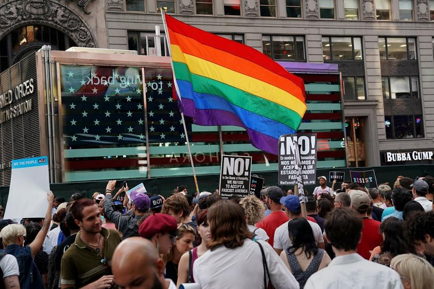 A rainbow flag flies as people protest US President Donald Trump's announcement that he plans to reinstate a ban on transgender individuals from serving in any capacity in the US military, in Times Square, New York City on July 26, 2017.