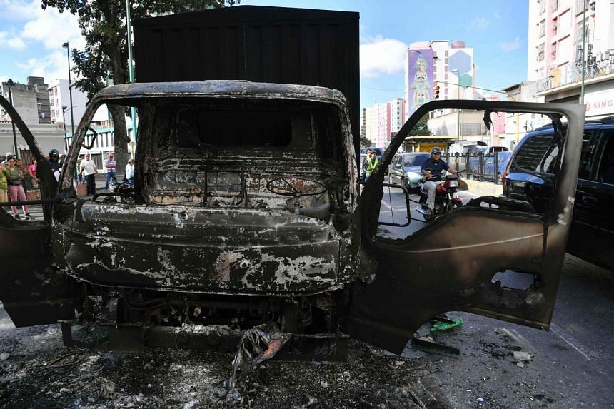 A motorcyclist drives past the wreckage of a government truck that was burned during protests.