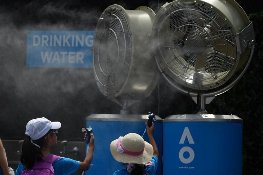 Spectators stand in front of mist fans as they hold handheld fans to cool down at the Australian Open tennis tournament in Melbourne on Jan 15, 2019.