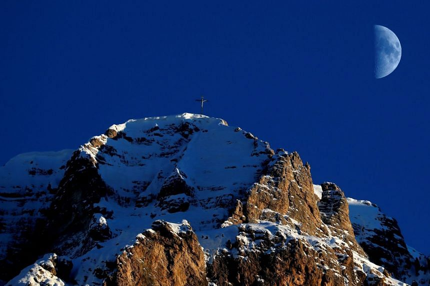 The moon rises over the alps in Val Gardena, northern Italy.