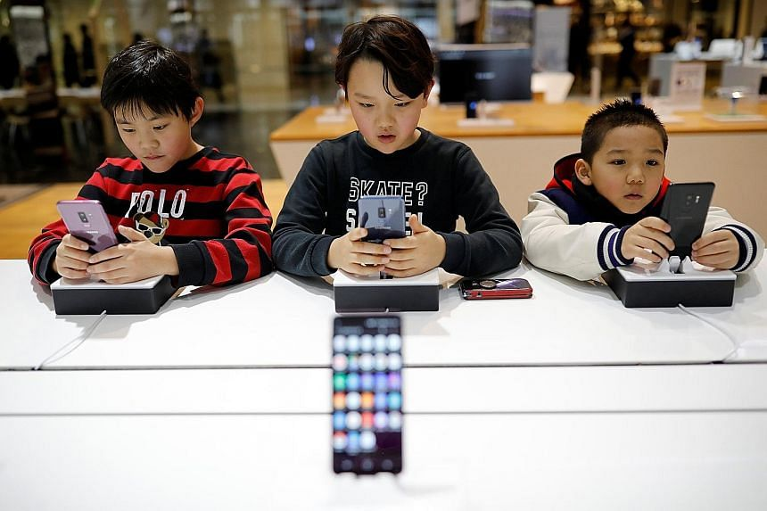 Children trying out Samsung Electronics' Galaxy S9 at its store in Seoul earlier this month. Samsung is expected to report downbeat fourth-quarter results on Jan 31.