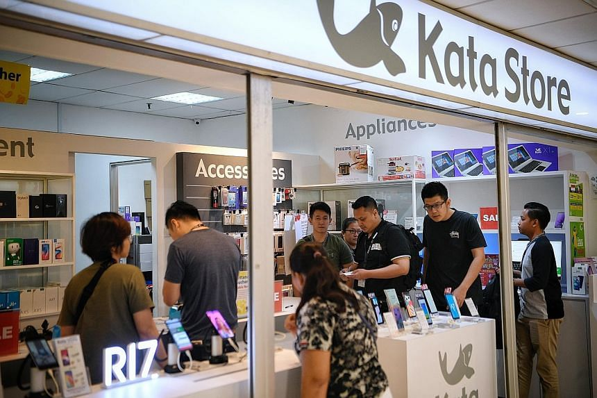 Police officers carrying out a raid on one of cellphone retailer Kata Store's three shops at Lucky Plaza yesterday. Kata, which is not a licensed moneylender, has a tie-up with remittance agency Brunphil Express.