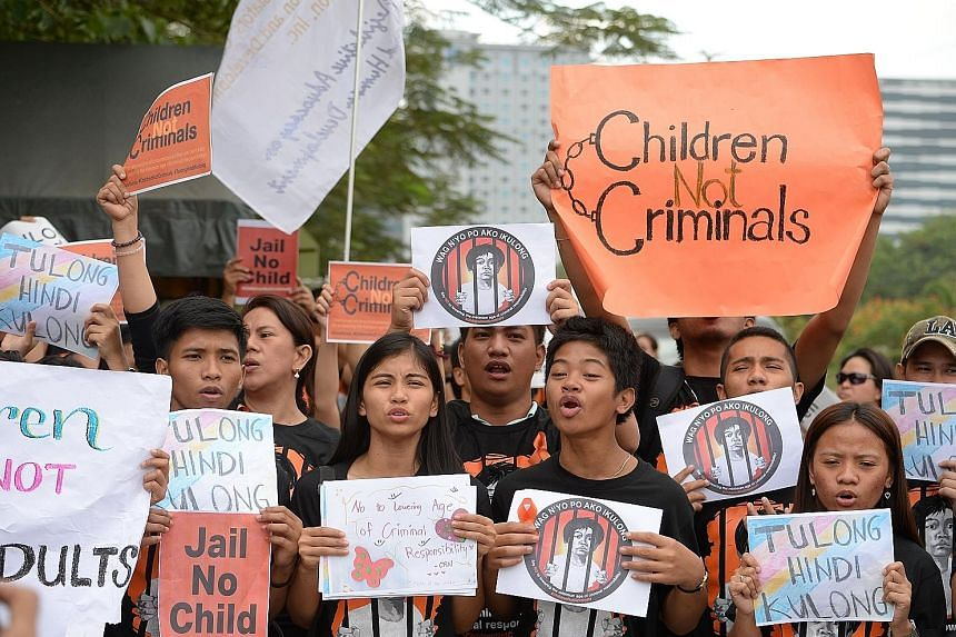 Activists in front of the Senate building in Manila yesterday rallying against the Bill to lower the age of criminal liability.
