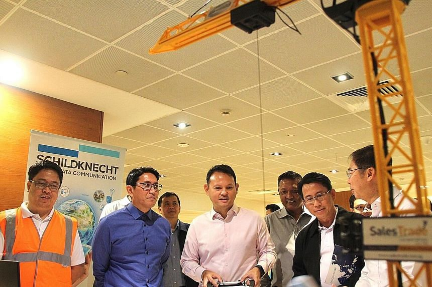 Minister of State Zaqy Mohamad (centre) trying out Salestrade Corporation's radio control system, which lets an operator control a crane remotely. With him are (from left) Mr Ismadi Mohd (in dark blue shirt), director, OSH Specialist Department, Occu